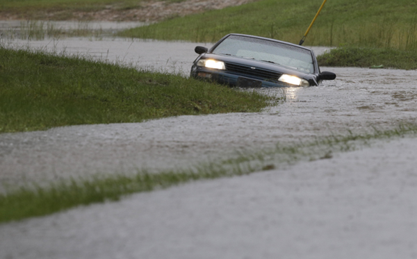 a car going through a heavily flooded road