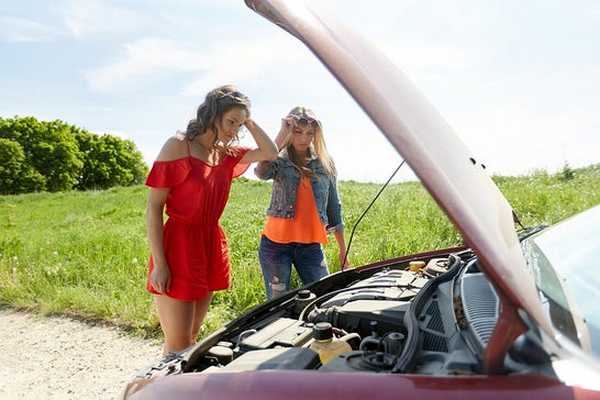 two-women-checking-the-car-engine