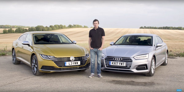 Man-standing-with-an-audi-and-volkswagen-sedans