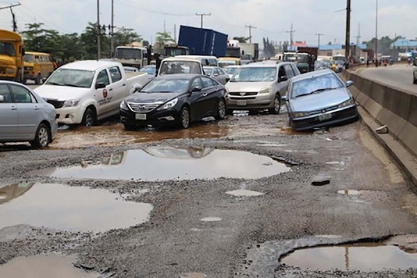 cars-driving-on-road-filed-with-potholes