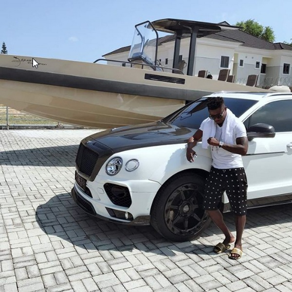 Obafemi-standing-by-his-Bentley